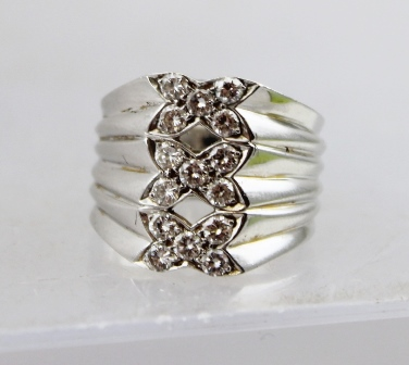 A HEAVY LADYS DRESS RING set with fifteen diamonds arranged in three bow setting, unmarked, considered to be 18ct, ring size M
