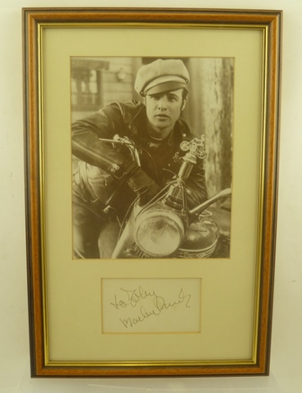 MARLON BRANDO (1924 - 2004) A studio portrait as Johnny in The Wild One, 1953 film, mounted with an autograph below in stained wood frame, mounted and glazed, image size 25cm x 20cm