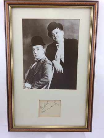 STAN LAUREL (1890 - 1965) AND OLIVER HARDY (1892 - 1957)  A black and white studio portrait of the double act in costume, mounted with a sheet of paper signed by both, Laurel and Hardy in stained wood frame, mounted and glazed, image size 25cm x 20cm