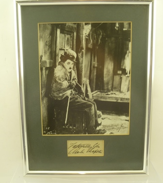 CHARLIE CHAPLIN (1889 - 1977) A black and white portrait of him on the set of The gold Rush, 1925, mounted with an autograph panel below in silvered frame, mounted and glazed, image size 24cm x 19cm