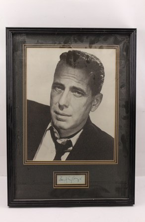 HUMPHREY BOGART (1899 - 1957) A black and white studio portrait mounted with his autograph below, in ebonised frame, mounted and glazed, image size 34cm x 27cm