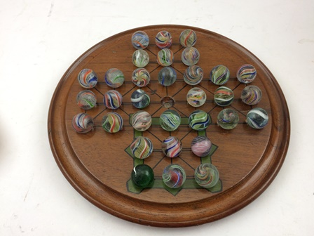 THIRTY-TWO HAND-MADE GLASS MARBLES together with a mahogany SOLITAIRE BOARD