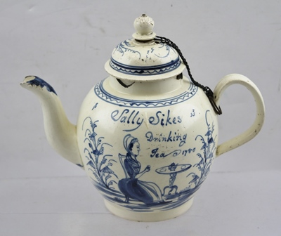 AN 18TH CENTURY CREAMWARE TEAPOT, fitted domed cover, secured on a chain to the strap work handle, hand painted cobalt blue decoration includes a landscape with cottage to one side, and to the other a lady seated taking tea, inscribed Sally Sikes drinking tea 1780, 17.5cm high (This teapot has been in the vendors family from the beginning, his mother took it to the Antiques Roadshow in the 1990s and David Battie included it in his BBC Pocket Guide, Pottery and Porcelain Book, of which a copy is offered with the teapot)