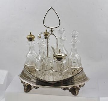 A VICTORIAN CUT GLASS SIX BOTTLE CRUET SET in a boat shaped silver plated frame