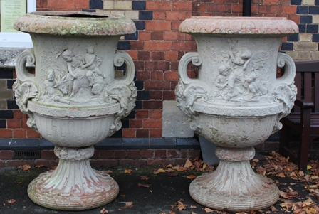 A PAIR OF SUBSTANTIAL LATE 20TH CENTURY CAST TERRACOTTA GARDEN URNS of campagna form, decorated with putti in the round, and having scroll handles with winged Bacchanalian masks, raised on outswept fluted bases with bound reed rims, 132cm high