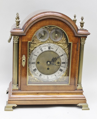 A GEORGIAN DESIGN TWIN FUSEE BRACKET CLOCK, having dome topped mahogany case with brass columns and finials, side carrying handles, pierced brass grilles and standing upon brass bracket feet, the 8-day striking movement with decoratively engraved back plate, the arched face with silvered chapter ring with Roman enumerated hours and Arabic minutes, to the arch a chime/silent indicator and a chime choice indicator Eight Bells or Chime as St. Marys Cambridge, case 46cm high