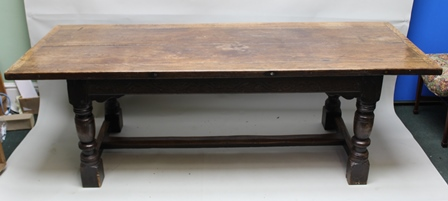 AN 18TH CENTURY OAK REFECTORY TABLE (with later alterations), having plank top upon a base with chip carved apron frieze, shaped cheeks, upon ring turned supports with plain stretchers, 228cm x 84cm