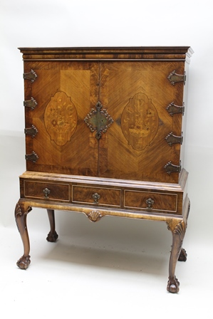 A DUTCH STYLE, GEORGIAN DESIGN CABINET ON STAND, having marquetry inlaid walnut banded doors with decorative metal work hinges and escutcheon, interior fitted shelves and drawers, on a base with two fitted drawers over a scallop crest apron, on cabriole legs with ball and claw feet, top 97cm wide x 137cm high