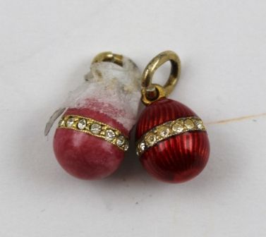 TWO RUSSIAN YELLOW METAL CHARM PENDANTS OF OVOID FORM, one red the other pink guilloche enamel, waisted with a band of diamond effect stones, ring suspensions indecipherably marked, the ovoid form 1cm high