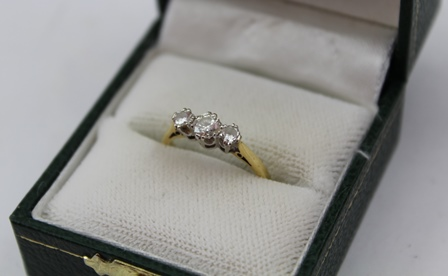 A THREE-STONE DIAMOND RING, having brilliant cut stones in a claw setting, 18ct gold band, size K