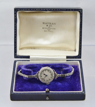 A LADYS EVENING WATCH, 18ct white gold case with silvered dial, bearing Arabic numerals, the bezel set eighteen cut diamonds, on a fancy 9ct white gold, close gate link bracelet with fold over clasp in a Nathan & Co, Birmingham and Solihull vendorsbox