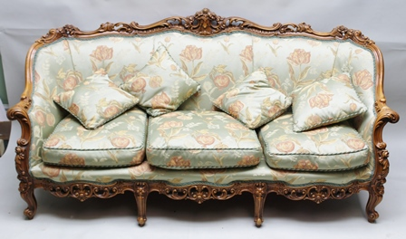 A LOUIS XV STYLE CARVED SHOW WOOD FRAMED THREE-SEATER SOFA, upholstered in a celadon green ground fabric, with blossoms and pomegranate decoration, with three seat cushions