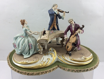 A CAPO-DI-MONTE PORCELAIN FIGURE GROUP OF A MUSICAL TRIO in 18th century costume, with cello, violin and a lady at the piano, on a gilt scroll base, limited edition no. 13, signed, raised upon a further fabric covered base, approximately 33cm wide x22cm high