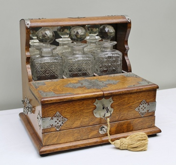 AN EDWARDIAN OAK TANTALUS fitted with three cut glass decanters, with metal mounts and drawer to base, 36cm wide