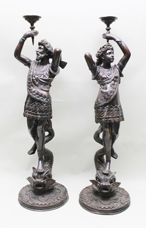 A PAIR OF CLASSICAL DESIGN BRONZE FIGURES, male and female, in decorative robes, wreaths to their hair, holding aloft  torch stands, standing upon stylized sea serpents, upon circular scallop shell cast bases, 148cm high