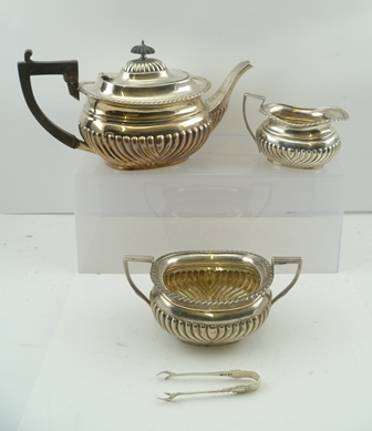 WILLIAM AITKIN AN EDWARDIAN THREE PIECE SILVER TEASET of Georgian fluted design, comprising; teapot, two-handled sugar bowl and milk jug, Birmingham, the teapot 1903, the other two items Birmingham 1902, combined weight (including non-silver teapothandle and knop), 1,121g (together with a pair of silver sugar nips)