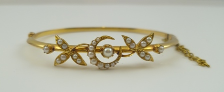 AN 18CT GOLD BANGLE decorated with a seed pearl inset crescent, flanked by seed pearl inset leaves, fitted safety chain, cased