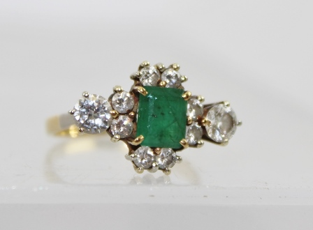 A DIAMOND AND EMERALD DRESS RING, the central facet cut emerald framed by eight small diamonds and two brilliant cut, larger diamonds to the shoulders, yellow metal band, ring size K tight