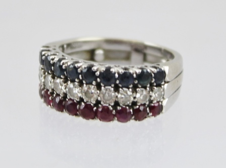 A LADYS DRESS RING, mounted with three bands of cut stones, ten stones in each line, diamonds, sapphires and rubies, mounted in an 18ct white gold band, size K 1/2