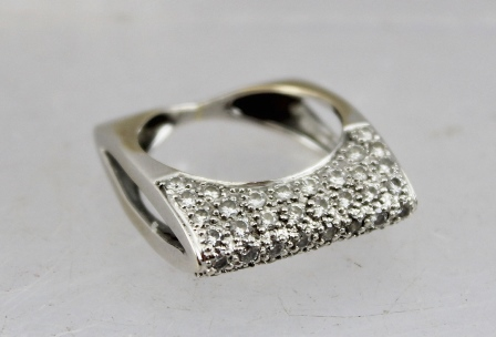 A CONTEMPORARY DESIGN DIAMOND SET RING in a white metal elliptical sided shank, size K and half