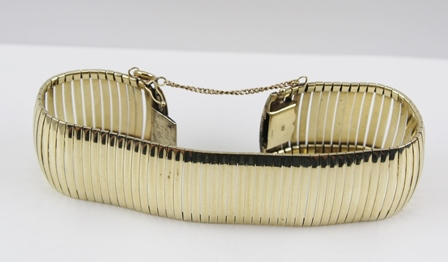A 9CT GOLD BRACELET of sectional form, 2.3cm wide (with safety chain), weighs 29g.