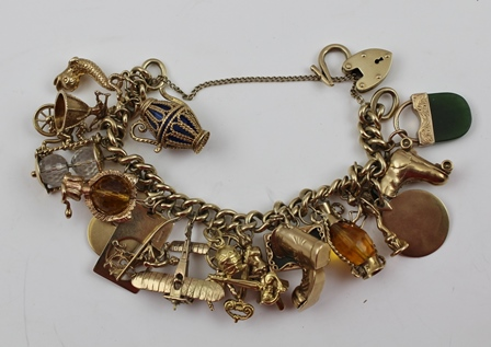 A 9CT GOLD CHARM BRACELET with padlock clasp, set with many and varied charms, some marked 9ct gold, others we describe as yellow metal, total weight 110g. (this does include some non-silver items