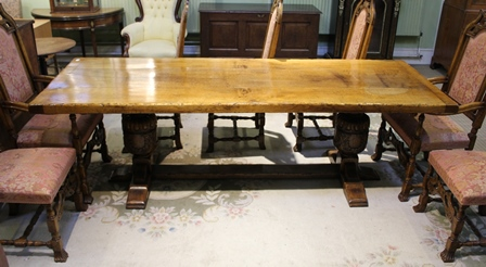 AN ELIZABETHAN DESIGN OAK TRESTLE FORM REFECTORY DINING TABLE, having plank top, raised on carved cup and cover supports with plain cross stretcher, 243cm x 88cm