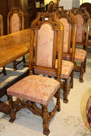 A SET OF EIGHT OAK FRAMED DINING CHAIRS each with carved crest, upholstered seat and back pad, comprising a pair of carvers and set of six singles