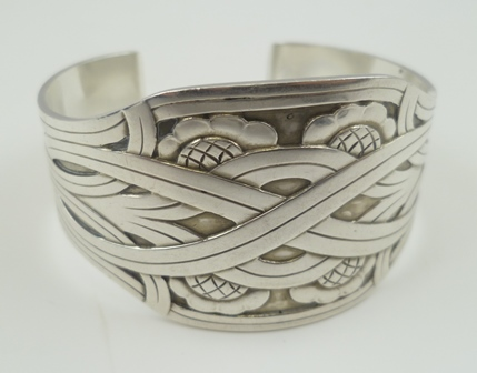 A GEORG JENSEN DANISH SILVER CUFF BANGLE, Art Nouveau band and flower head decoration, various stamp marks, 58g.