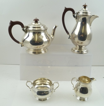 SELFRIDGE & CO. LTD. A GEORGIAN DESIGN FOUR PIECE SILVER TEASET comprising; teapot, hot water jug, milk jug and sugar bowl, of plain baluster form with decorative rims, composition, heat resisting (non-silver) handles to teapot and hot water pot, also knops to the hinged covers, Birmingham 1933, combined weight 1,443g