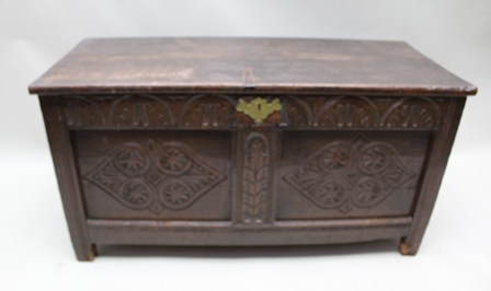 AN 18TH CENTURY OAK COFFER, having twin planked lift-up lid on later Victorian carved frontage, having twin panels, the vacant interior having associated candle box, 59cm x 114cm