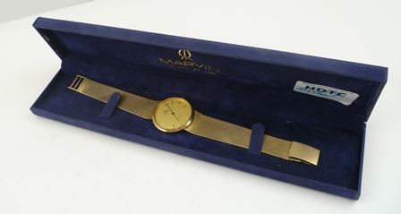 A MARVIN REVUE GENTLEMANS GOLD WRIST WATCH with bracelet strap, the dial champagne with baton indices, quartz movement, in original vendors box