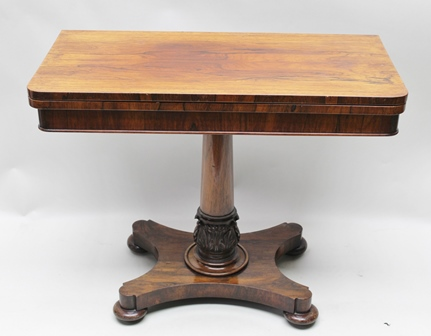 A 19TH CENTURY ROSEWOOD FOLD-OVER CARD TABLE, raised on tapering stem with carved acanthus leaf base, on shaped platform and bun feet, 92cm wide