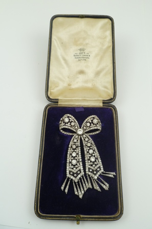 A DIAMOND BROOCH of bow form, with tassel ends, set with various sized brilliant cut stones in a white metal setting, with pin fitting, 8cm long, bow 4.2cm across, in a Jays of Oxford Street, London Diamond Merchants box