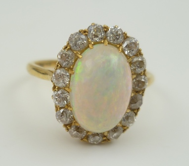 A LADYS DRESS RING, opal set, framed by fifteen brilliant cut diamonds in a yellow metal setting, ring size S, boxed
