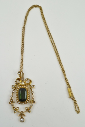 A DECORATIVE VICTORIAN DESIGN PENDANT, the yellow metal hinged form frame set with diamonds and seed pearls about a central facet cut cushion stone, on yellow metal chain