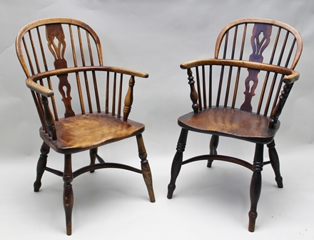 TWO 19TH CENTURY LOW STICK BACK WINDSOR DESIGN ARMCHAIRS with pierced splat backs, elm seats, on ring turned supports with crinoline stretchers