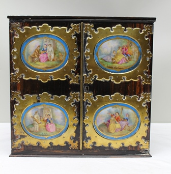 A 19TH CENTURY COROMANDEL TABLE CABINET with decorative brass mounts and side carrying handles, the twin doors set with oval painted porcelain panels in the Sevres style, opens to reveal drawers and shelves, 40cm wide