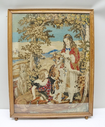 A VICTORIAN WOOLWORK PANEL, depicts children with dogs and a deer in a parkland setting, mounted in an oak edge mount glazed frame, 85cm x 65cm