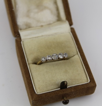 A GRADUATED FIVE STONE DIAMOND RING, brilliant cut, set upon a yellow metal band, size K (with ring box)