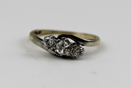 A THREE STONE DIAMOND RING, brilliant cut, set in a platinum mount, on 9ct band, ring size K 1/2