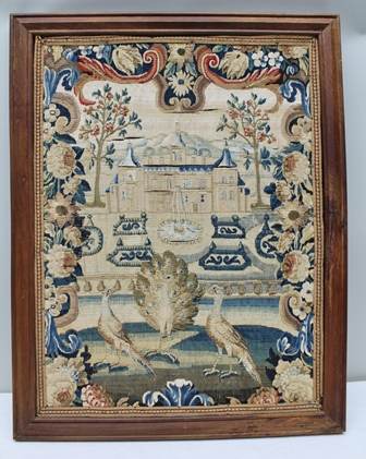 A LATE 18TH/EARLY 19TH CENTURY BELIEVED CONTINENTAL TAPESTRY, depicting a palatial dwelling in formal gardens, with peacocks in the foreground, having floral frame in a variety of wool and cotton stitching displaying a variety of techniques, 63cm x 48cm in moulded wooden frame