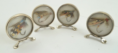 GREY AND CO. A CASED SET OF FOUR EDWARDIAN SILVER MOUNTED MENU OR PLACE MARKERS of circular form, each one containing a different tied fishing fly, Birmingham 1907, contained within their own fitted black case