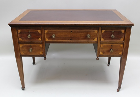 AN EDWARDIAN MAHOGANY WRITING TABLE fitted one long and four small drawers with brass knob handles, raised on square tapering supports, 107cm wide