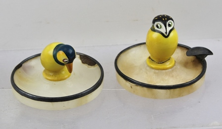 TWO ROYAL DOULTON CAKE MODELS, a penguin and an owl, each glazed in yellow, 45mm high and 32mm high, and TWO SILVER RIMMED AGATE ASHTRAYS, 75mm diameter