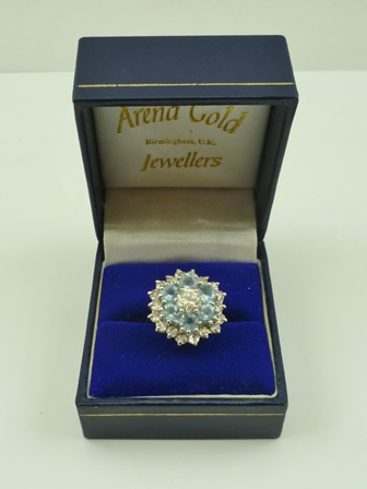 A DIAMOND AND AQUAMARINE CLUSTER RING of flower head design, central diamond approx. half carat, set upon an 18ct gold band