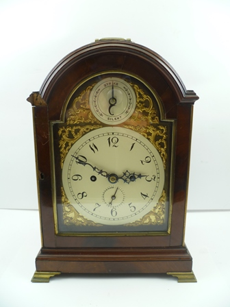 A GEORGIAN DESIGN MAHOGANY CASED MANTEL CLOCK, the case with brass handle and pierced fish scale grilles, raised on brass ogee feet, the arched top dial with strike/silent indicator, the dial with Arabic numerals and date indicator, fitted an 8-day twin fusee striking movement, the movement back-plate engraved with The Prince of Wales feathers, 38cm high