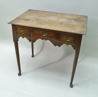 AN 18TH CENTURY OAK LOWBOY, having three fitted drawers, brass shaped back plate handles, raised on turned tapering supports with pad feet, 71cm wide