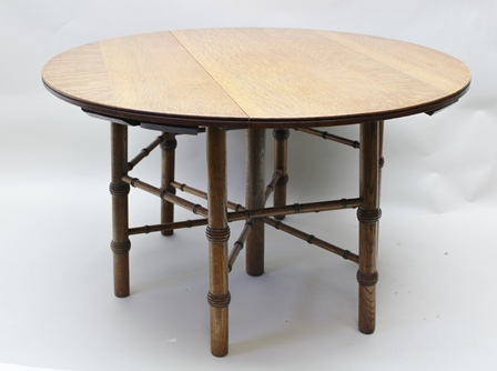 PHILIP WEBB (1831 - 1915) AN ARTS AND CRAFTS OAK CENTRE TABLE, designed in 1865, the circular plank top raised on plain centre leg and six outer, ring turned legs with confirming radial and half height perimeter stretchers, 73cm x 123cm, labelled to underside Holliday Son & Co, Cabinets Makers, Birmingham