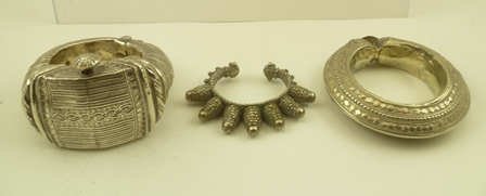 A SUBSTANTIAL WHITE METAL BEDOUIN BRACELET of hinged design, having pegged clasp, together with two other decorative BRACELETS (30